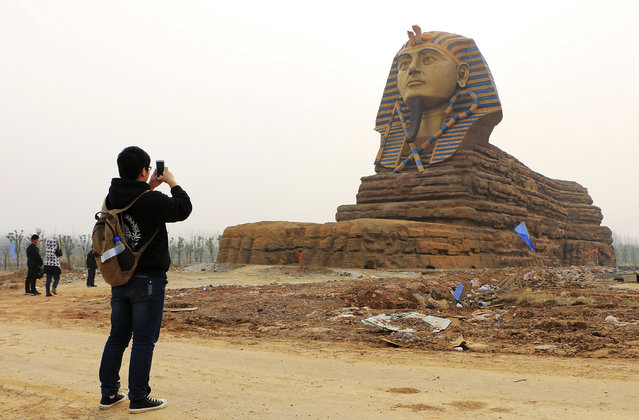 A man takes pictures of a full scale replica of the sphinx, which is part of an unfinished movie and animation tourism theme park, in Chuzhou, Anhui province, China, March 3, 2015. (Photo by Reuters/Stringer)