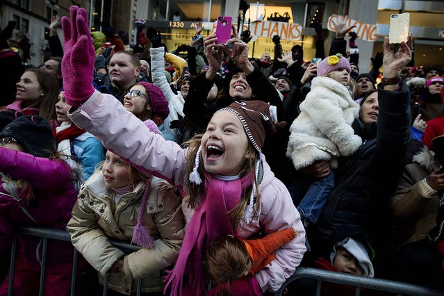 Spectators watch the parade. (Photo by John Minchillo/Associated Press)