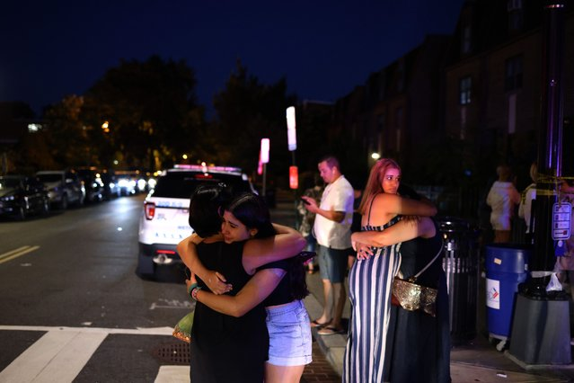 People embrace near the site of a shooting on July 22, 2021 in Washington, DC. Gunfire erupted on a busy street, injuring two and sending others fleeing for safety. A dark sedan was being sought in connection with the shooting and the two injured were expected to survive, according to published reports. (Photo by Anna Moneymaker/Getty Images)