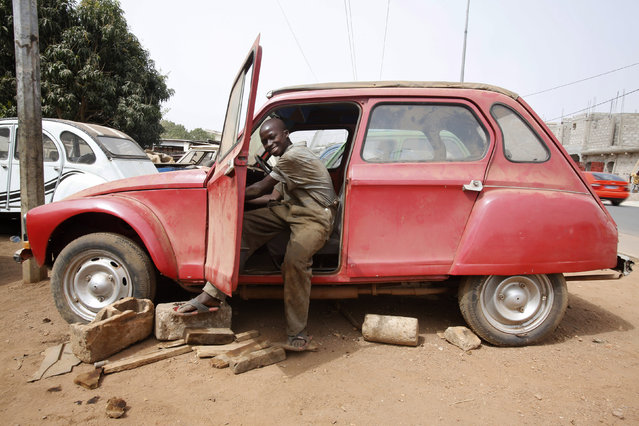 A boy works on a car in Babi Kouakou's car repair garage in Bouake, Ivory Coast February 9, 2016. Babi specialises in restoring old cars. (Photo by Thierry Gouegnon/Reuters)
