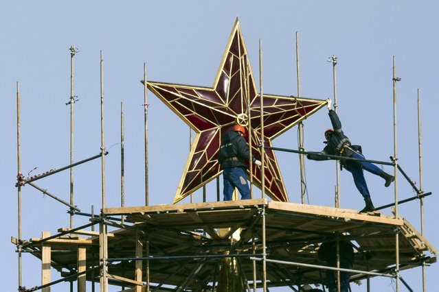 Workers stand on scaffolding around the top of the Kremlin's Spasskaya Tower to renovate it, in Moscow, Russia, Tuesday, April 7, 2015. (Photo by Pavel Golovkin/AP Photo)