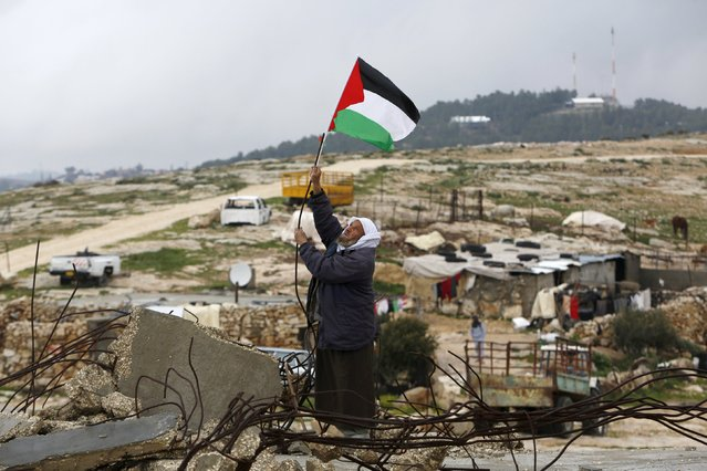 A Palestinian man hangs a Palestinian flag atop the ruins of a mosque, during a snow storm in West Bank village of Mufagara, south of Hebron January 27, 2016. (Photo by Mussa Qawasma/Reuters)