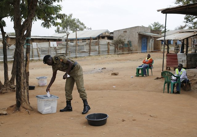 A police officer casts his ballot at a polling station during elections in a village near the town of Kaabong in Karamoja region, Uganda February 18, 2016. (Photo by Goran Tomasevic/Reuters)