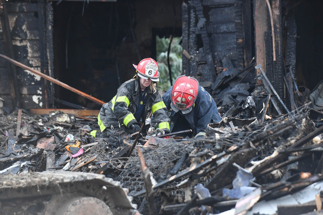 Firefighters sift through debris at the scene of an overnight house fire, where several children were presumed dead and others including the mother injured, in Baltimore, Maryland, U.S., January 12, 2017. (Photo by Bryan Woolston/Reuters)