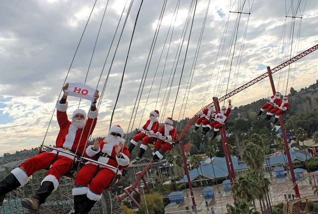 In this December 18, 2013 photo released by Six Flags Discovery Kingdom, 32 men dressed as Santa Claus ride the 150-foot tall SkyScreamer tower swing ride at Six Flags Discovery Kingdom in Vallejo, Calif. (Photo by Jason Quintos/AP Photo/Six Flags Discovery Kingdom)
