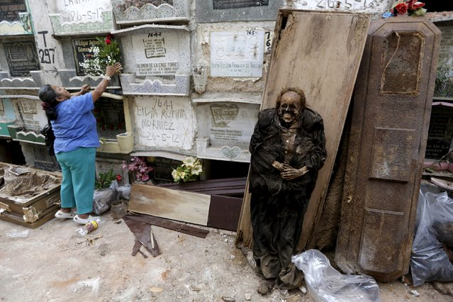A woman (L) places flowers at a grave next to a mummified body during exhumation works at the General Cemetery in Guatemala City, April 15, 2015. (Photo by Jorge Dan Lopez/Reuters)