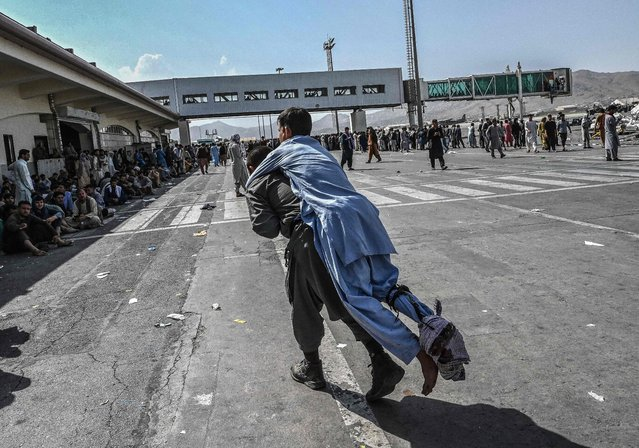 A volunteer carries an injured man as other people can be seen waiting at the Kabul airport in Kabul on August 16, 2021, after a stunningly swift end to Afghanistan's 20-year war, as thousands of people mobbed the city's airport trying to flee the group's feared hardline brand of Islamist rule. (Photo by Wakil Kohsar/AFP Photo)