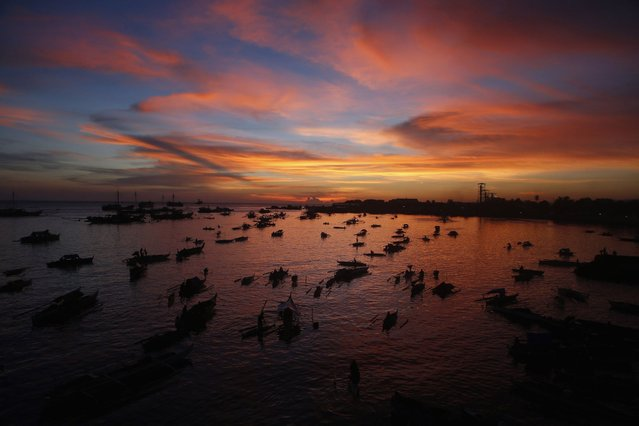 A flotilla of bancas (locally made boats) carrying evacuees displaced from their homes due to fighting between government soldiers and Muslim rebels from the Moro National Liberation Front (MNLF), is seen during sunset at a wharf in Zamboanga city, southern Philippines September 14, 2013. (Photo by Erik De Castro/Reuters)