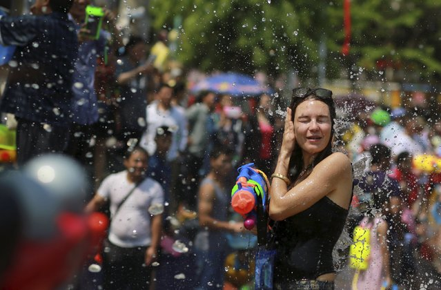 A woman wipes her head as she holds a water gun during the annual water-splashing festival in Xishuangbanna, Yunnan province, April 15, 2015. Thousands of people participated in the festival on Tuesday to celebrate the 1,377th ethnic Dai minority New Year, local media reported. (Photo by Reuters/Stringer)