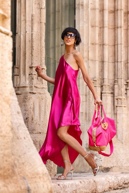 German-based model and artist Zoe Helali wearing a fuchsia colored Beatrice silk dress with open one shoulder, loose silhouette and asymmetric hem by Sasha La Mer, silver high heel sandals with crystals by Pedro Garcia, a hot pink Jessie Clipper scotchgrain bag by Mulberry and dark blue Kate sunglasses by Saint Laurent during a street style shooting on August 23, 2021 in Palma de Mallorca, Spain. (Photo by Streetstyleshooters/Getty Images)