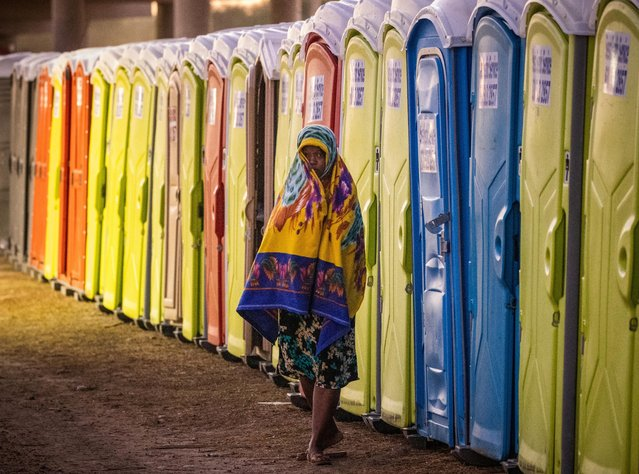 A migrant woman walks past a row of portable toilets at a makeshift border camp along the International Bridge in Del Rio, Texas, U.S. September 23, 2021. (Photo by Adrees Latif/Reuters)