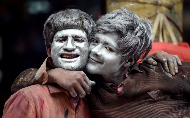Indian coloured powder vendors pose for photographs as they coloured their face for the upcoming spring festival of Holi in New Delhi on March 13, 2019. Holi, also called the festival of colours, is a popular Hindu spring festival observed in India at the end of winter season. (Photo by Money Sharma/AFP Photo)