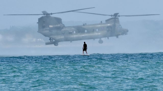 Howard Shepherd was taking photos of his surfer friend, Toby Irons in Dorset, southwest England on June 25, 2021 when the huge Chinook appeared hovering above the sea just 200 yards away. (Photo by Howard Shepherd/BNPS)