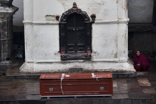 A woman sits near an empty coffin at the Pashupatinath temple on the banks of the Bagmati River in Kathmandu, Nepal, Tuesday, April 28, 2015. (Photo by Bernat Armangue/AP Photo)