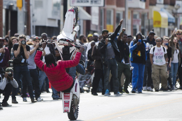 A motorcyclist rides Tuesday, April 28, 2015, in Baltimore. Maryland's governor vowed there would be no repeat of the looting, arson and vandalism that erupted Monday in some of the city's poorest neighborhoods. (Photo by Matt Rourke/AP Photo)