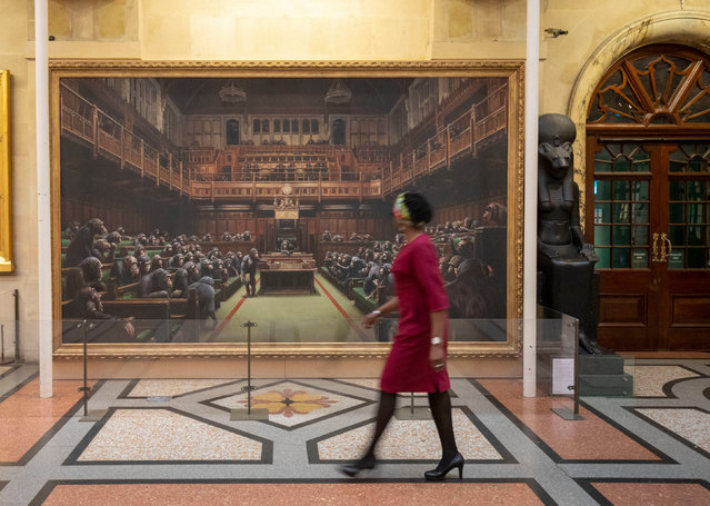 A passerby views the painting Devolved Parliament, by the graffiti artist Banksy, which is going on show at Bristol Museum in England on March 28, 2019. (Photo by Steve Parsons/PA Wire Press Association)