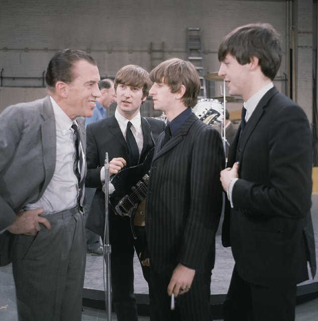 "The British rock and roll group the Beatles talk to Ed Sullivan at CBS Studio 50 before their live television appearance on ""The Ed Sullivan Show"" in New York, February 10, 1964. From left to right are, Sullivan, John Lennon, Ringo Starr, holding a cigarette, and Paul McCartney. (Photo by AP Photo)"