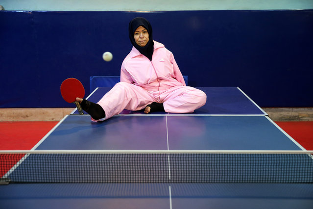 """In this picture taken on Sunday, January 18, 2015, Zohreh Etezadossaltaneh plays ping pong using her foot to hold the paddle in a sport club in Tehran, Iran. """"I want to play seriously and get a name"""", she said. """"I want to represent my country in competitions overseas"""". (Photo by Ebrahim Noroozi/AP Photo)"""
