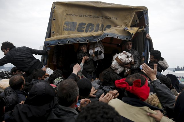 Refugees and migrants grab goods donated by volunteers from a truck at a makeshift camp at the Greek-Macedonian border, near the village of Idomeni, Greece March 16, 2016. (Photo by Alkis Konstantinidis/Reuters)