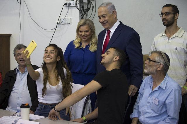 Israel's Prime Minister Benjamin Netanyahu poses for a photo with his wife Sara after voting during Israel's parliamentary elections in Jerusalem, Tuesday, April 9, 2019. (Photo by Ariel Schalit/AP Photo)