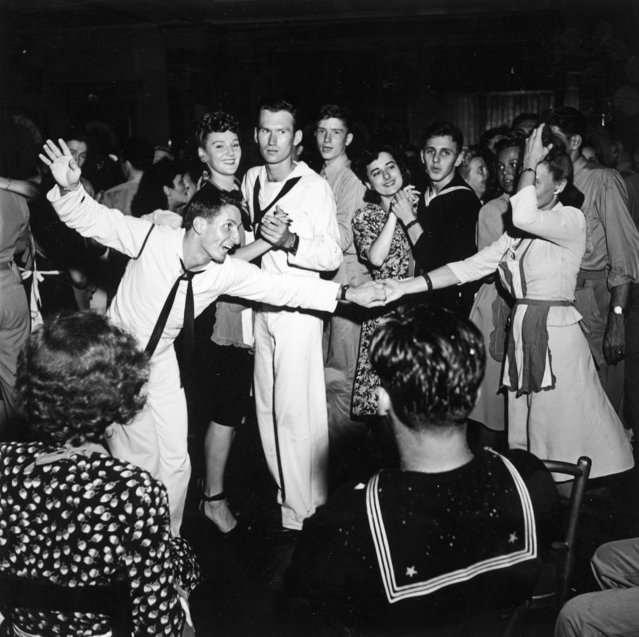 A sailor tries to entice a woman in an apron to dance while other sailors dance with their partners on VE Day, World War II, 8th May 1945. (Photo by Archive Photos/Getty Images)