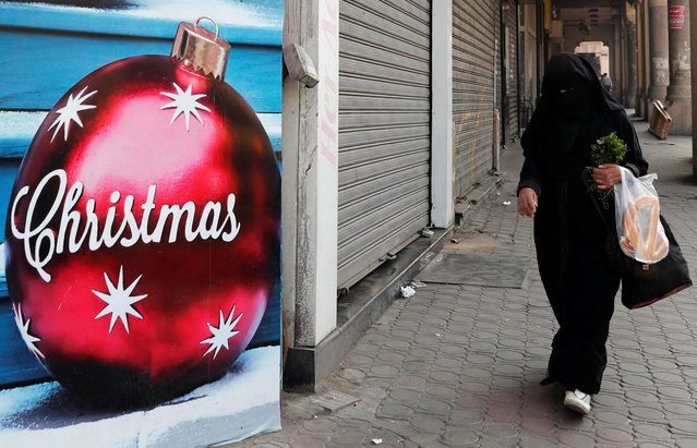 An Egyptian woman wearing a full veil (niqab) walks in front of a Christmas decorations shop in Cairo, Egypt December 3, 2018. (Photo by Amr Abdallah Dalsh/Reuters)