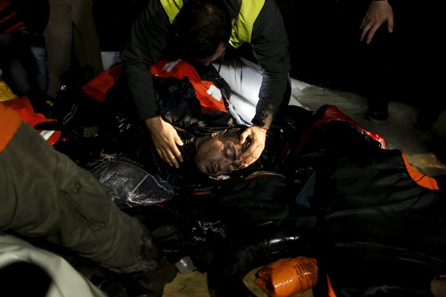A rescuer checks on an unconscious refugee as refugees and migrants arrive on a dinghy on the shore near the city of Mytilene on the Greek island of Lesbos, March 20, 2016. (Photo by Alkis Konstantinidis/Reuters)