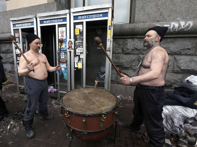 Two anti-government protesters use a large drum after violence erupted in the Independence Square in Kiev, on February 20, 2014. (Photo by Vasily Fedosenko/Reuters)
