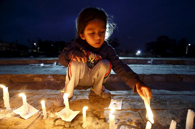 A boy lights a candle during a candle light vigil to remember the victims of last week's earthquake in Kathmandu, Nepal 2 May 2015. (Photo by Navesh Chitrakar/Reuters)