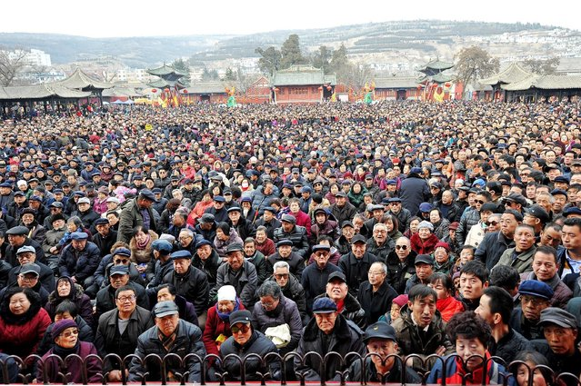 People watch folk artists perform an local opera during a performance ahead of Lantern Festival, to celebrate Lunar New Year, in Tianshui, Gansu province, China, February 10, 2017. (Photo by Reuters/Stringer)