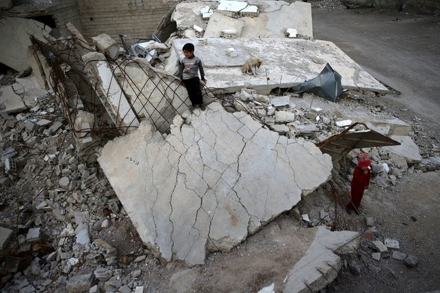 Children play on rubble of damaged buildings in the rebel held besieged town of Douma, eastern Damascus suburb of Ghouta, Syria March 19, 2016. (Photo by Bassam Khabieh/Reuters)