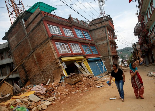 Women walk past a building damaged by earthquakes, causing it to lean to a side, in Sindhupalchowk district, Nepal, May 13, 2015. (Photo by Ahmad Masood/Reuters)