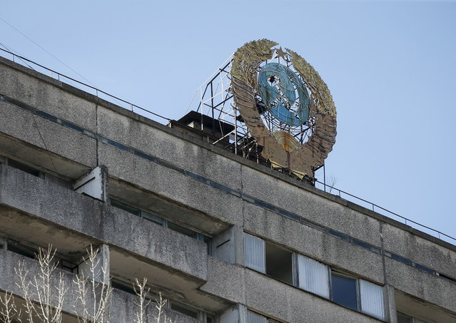The coat of arms of the former Soviet Union is seen on the roof of a house in the abandoned city of Pripyat near Chernobyl nuclear power plant in Ukraine on March 29, 2016. (Photo by Gleb Garanich/Reuters)