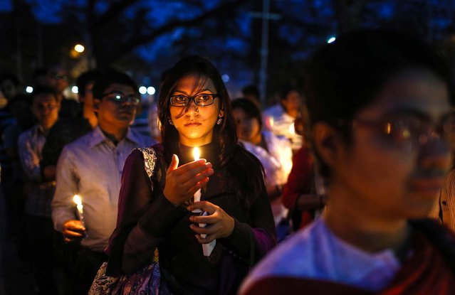 People hold candles as they pay homage to the victims of the 2011 earthquake and tsunami in Japan, during a ceremony in Dhaka, Bangladesh, on March 10, 2014. Tuesday marks the third anniversary of the earthquake, tsunami and nuclear disaster known as 3.11 that killed 15,884 people and left 2,636 unaccounted for in vast areas of its northern coast. (Photo by A. M. Ahad/Associated Press)