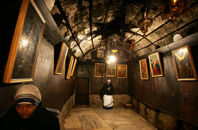 Nuns of the congregation of Mother Teresa of Calcuta pray inside the Grotto, on the site where Christians believe Jesus was born, within the Church of the Nativity in the West Bank town of Bethlehem Friday, December 23, 2005. (Photo by Oded Balilty/AP Photo)