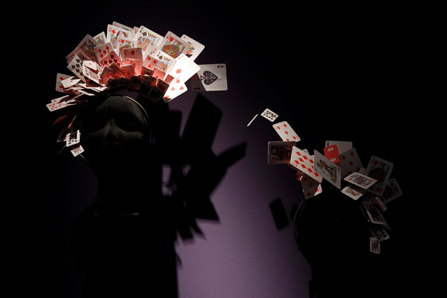"""Cards on display over a mannequin head during the exhibition """"The Designing 007: Fifty Years of Bond Style"""" during a press presentation at the Grande Halle de la Villette in Paris, France, April 13, 2016. (Photo by Benoit Tessier/Reuters)"""