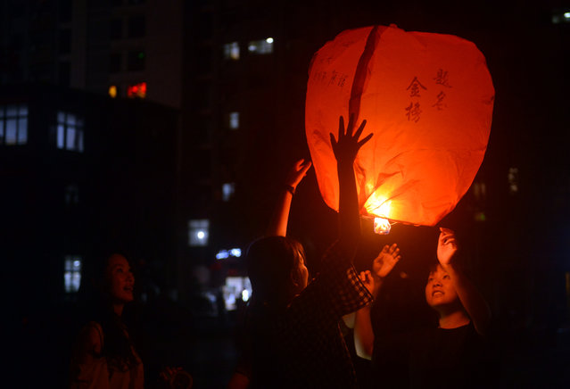 """Students release a sky lantern to pray for the upcoming annual national college entrance examination, or """"gaokao"""", in Maotanchang town of Luan, Anhui province, China on June 4, 2019. (Photo by Reuters/China Stringer Network)"""