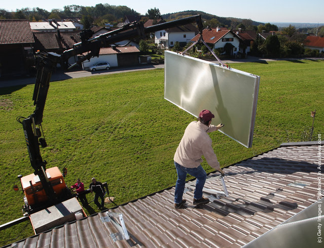 Workers install solar power modules for producing heat on the roof of a house