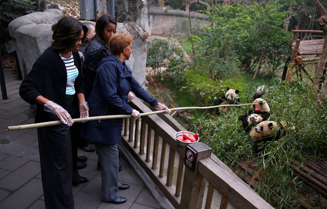 U.S. first lady Michelle Obama, left, and her mother Marian Robinson, right, feed apple to giant pandas during their visit at Giant Panda Research Base in Chengdu, Sichuan province, China Wednesday, March 26, 2014. (Photo by Petar Kujundzic/AP Photo)