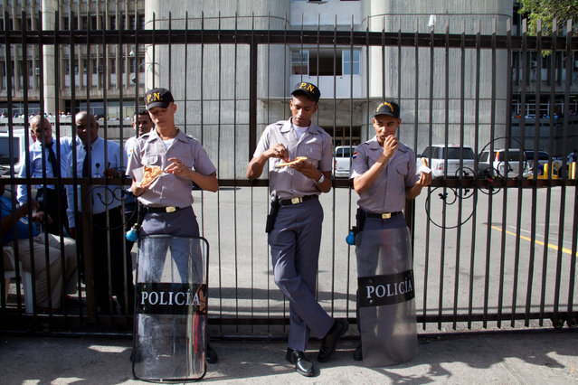 Police eat empanadas as they guard the Interior Ministry where people line up to register for legal residency in Santo Domingo, Dominican Republic, Tuesday, June 16, 2015. Army Gen. Rubel Paulino says his agency will patrol areas with large immigrant communities on Thursday following the end of a period in which non-citizens could apply for legal status. (AP Photo/Tatiana Fernandez)