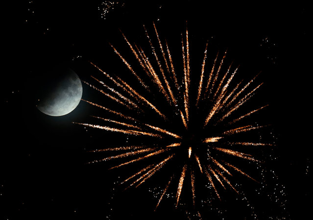 A partial lunar eclipse rise during a firework at the Brezel festival in Speyer, Germany, 16 July 2019. The partial lunar eclipse on the night of 16 July 2019 will take place 50 years after the astronauts Neil Armstrong, Buzz Aldrin and Michael Collins launched aboard a Saturn V rocket toward the Moon on 16 July 1969. The year 2019 marks the 50th anniversary of the first moon landing on 20 July 1969. (Photo by Ronald Wittek/EPA/EFE)