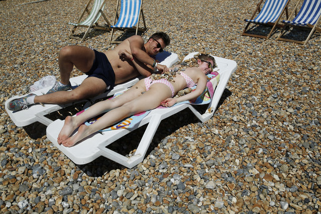 Hadley Eames covers Gemma Cousins with stones as they sunbathe on a hot Summer day at Brighton beach in Britain June 30, 2015. (Photo by Luke MacGregor/Reuters)