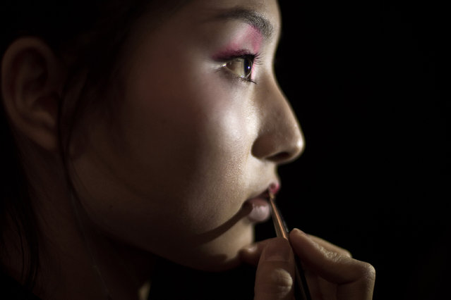 A model gets her make up done backstage before parading the Chenwen studio collection by Chen Wen during China Fashion Week in Beijing on March 29, 2017. (Photo by Nicolas Asfouri/AFP Photo)