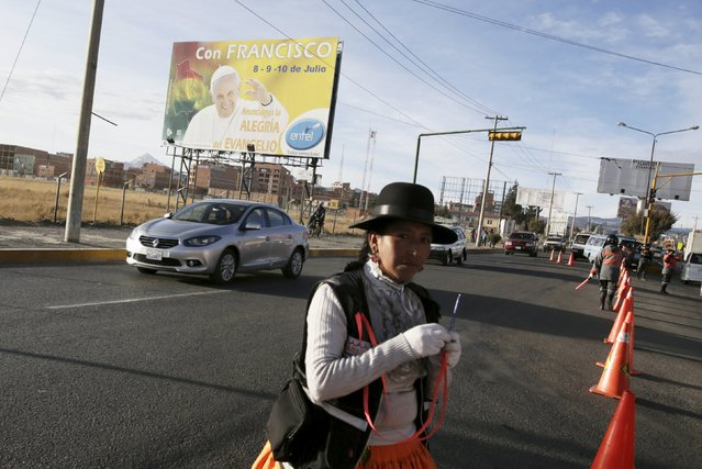 A traffic guard walks past as a bilboard announcing Pope Francis's visit is seen on the side of a road in El Alto July 2, 2015. When Pope Francis visits Bolivia next week, he will discover a nation that cherishes animal sacrifices and pagan worship and where relations between indigenous communities and the Roman Catholic Church have been strained. The country's first indigenous president, Evo Morales, has frequently clashed with the church. (Photo by David Mercado/Reuters)