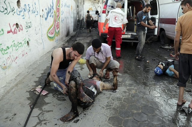 In this July 30, 2014 photo, neighbors help gravely injured Mohammed al-Selek, 39, wounded by an Israeli mortar strike as he lays next to the body of Palestinian journalist Rami Reyan who was killed, in the Shijaiyah neighborhood of the northern Gaza Strip. Al-Selek's life changed forever last July 30, when the shells slammed into his home killing all his three children, his father and six other relatives. (Photo by Adel Hana/AP Photo)
