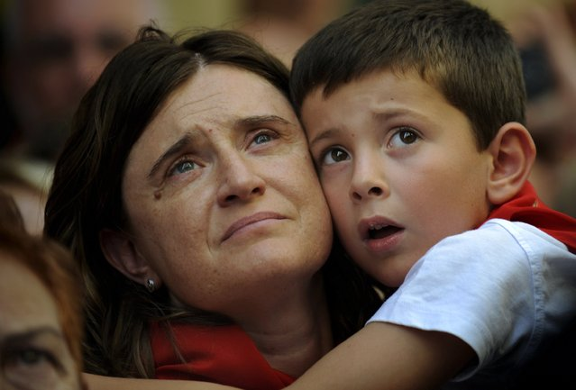 A woman and a boy look up during a procession in honour of San Fermin on the saint's day at the San Fermin festival in Pamplona, northern Spain, July 7, 2015. (Photo by Eloy Alonso/Reuters)