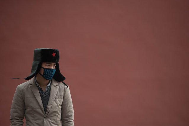 A man wearing face mask stands before a wall inside the Forbidden City during heavy pollution in Beijing on February 28, 2013. Beijing residents were urged to stay indoors as pollution levels soared before a sandstorm brought further misery to China's capital. (Photo by Ed Jones/AFP Photo)