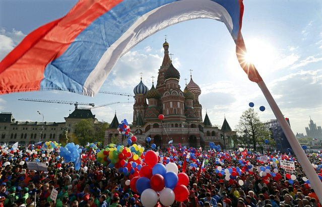 People walk with flags and balloons on Red Square during a rally in Moscow, Russia, 01 May 2014. Labour Day, also known as International Workers' Day or May Day, is observed worldwide on 01 May. (Photo by Yuri Kochetkov/EPA)