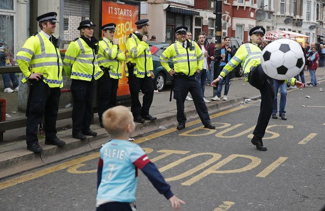 Britain Soccer Football, West Ham United vs Manchester United, Barclays Premier League, Old Trafford on May 10, 2016. Police play football with a young West Ham fan before the match. (Photo by Eddie Keogh/Reuters/Livepic)