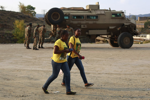 Two women wearing ANC shirts walk past a South African military vehicle stationed for security in Sterkspruit, Eastern Cape, South Africa, Wednesday, May 7, 2014. South Africa goes to the polls Wednesday in elections that are likely to see the ruling African National Congress (ANC) party return to power with a smaller majority due to voters disaffected by corruption in government and economic inequality. (Photo by Jerome Delay/AP Photo)